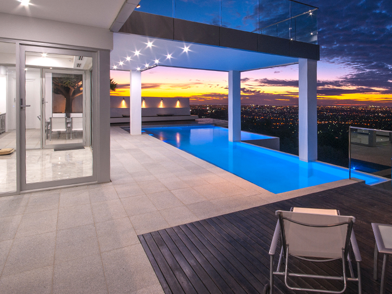 large infinity edge lap pool timber deck and outdoor entertainment area with city views the galvin group